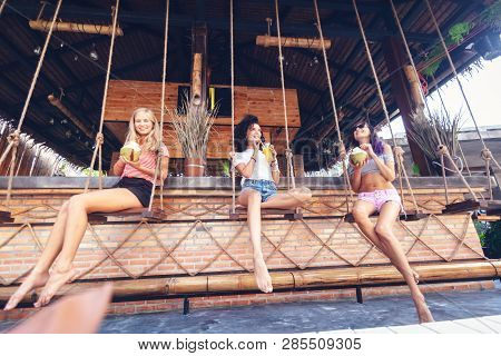 Three Young Beautiful Slender Girlfriends Drink Necks And Coconuts In A Stylish Beach Bar, At Bar Co