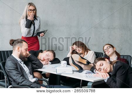 Tired Corporate Personnel. Overworking Concept. Colleague Looking At Team Members Sleeping On Desk A