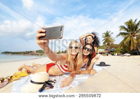 Beautiful Happy Girlfriends Having Fun On The Beach Taking Selfies During Vacation And Travel, Layin