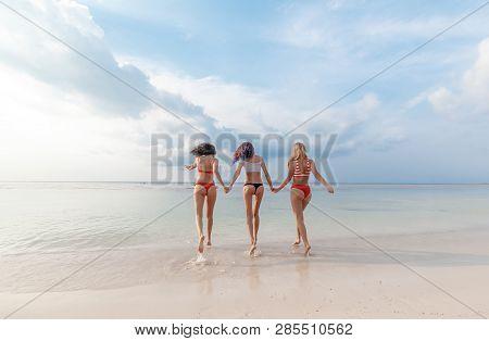 Three Beautiful Slender Happy Girlfriends Having Fun On The Beach Rejoicing And Having Fun Against T