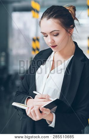 Company Employee Portrait. Business Matters. Young Intern Making Notes In Day Planner.