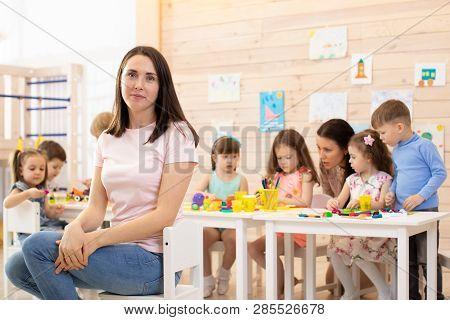Group Of Children And Educator Doing Handcrafting Together In Classroom In Kindergarten
