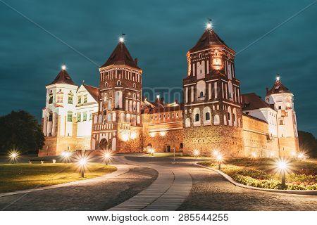 Mir, Belarus. Mir Castle Complex In Evening Night Illumination Lighting. Famous Landmark Under Blue