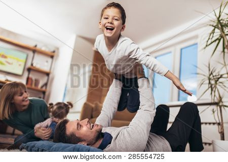 Happy Family Having Fun On Floor Of In Living Room At Home, Laughing, Selective Focus.