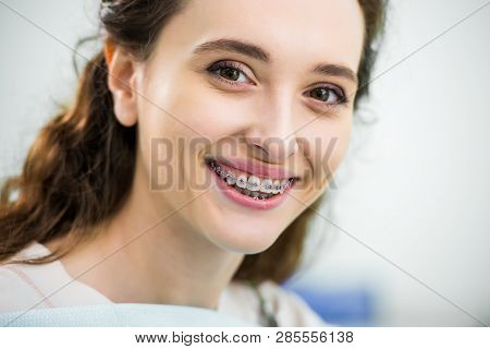 Close Up Of Happy Woman With Braces On Teeth Smiling In Dental Clinic