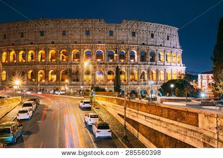 Rome, Italy. Colosseum Also Known As Flavian Amphitheatre In Evening Or Night Time. Night Traffic Li