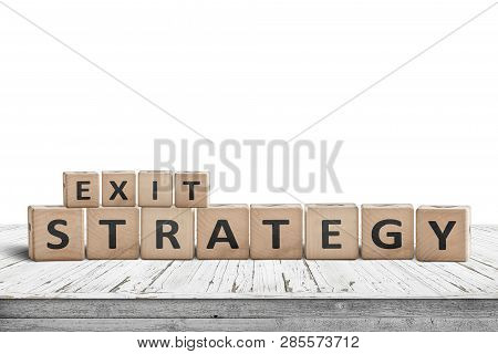 Exit Strategy Sign On A Wooden Desk Isolated On White