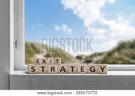 Exit Strategy Sign In A Window With A View To Beautiful Nature Under A Blue Sky