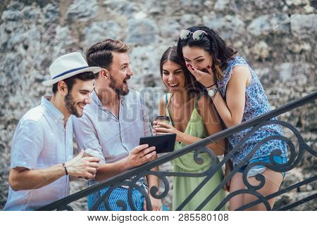 Group Of Young Tourist Friends With Digital Tablet Having Fun