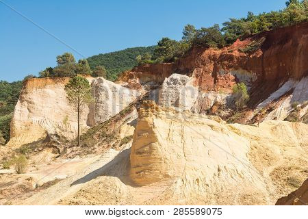 Tourists Visiting The Famous Ocra Color Quarries Near Roussillon In France During A Sunny Day
