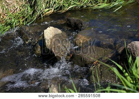 Stones In The Clear, Flowing Stream Surrounded By Whitecaps