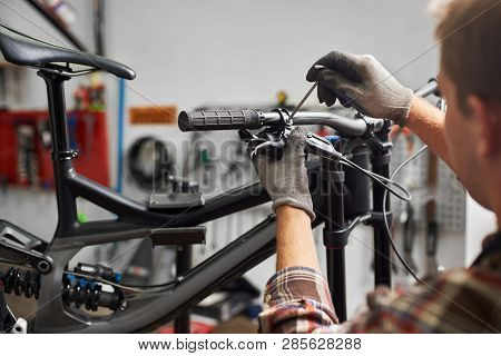 Cropped Shot Of Male Mechanic Working In Bicycle Repair Shop, Serviceman Repairing Modern Bike Using