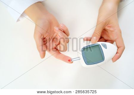 Image of woman's hand with glucometer.