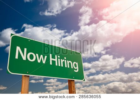 Now Hiring Green Road Sign Aginst Sky.
