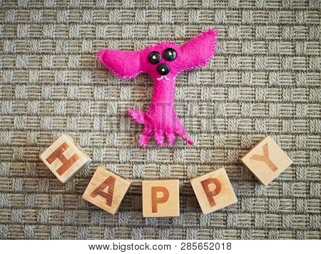 Handmade Toy Dog And Wooden Alphabet Blocks Spelling Happy On Grey Carpet. Educational Toys For Chil