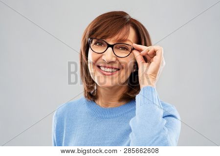 vision and old people concept - portrait of smiling senior woman in glasses over grey background