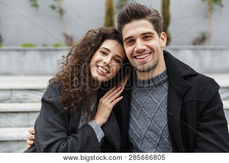 Image of lovely couple man and woman 20s in warm clothes hugging while sitting on stairs outdoor