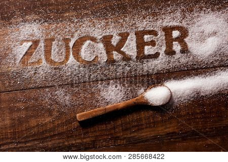 high angle view of a wooden table sprinkled with sugar where you can read the word zucker, sugar written in German, and a spoon full of sugar