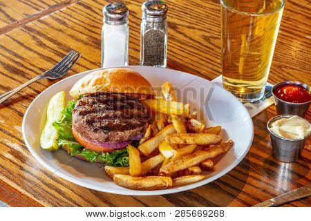 Home made hamburger with beef, onion, tomato, lettuce and cheese. Fresh burger closeup on wooden rustic table with potato fries, beer and chips. Cheeseburger