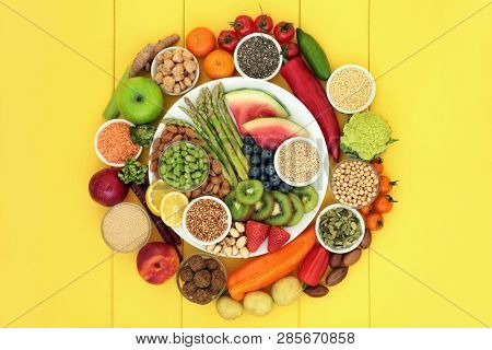 Vegan health food with fresh fruit and vegetables, grains, nuts, seeds, sos mix, quinoa balls, spice and legumes. Super foods high in antioxdants, protein, vitamins and dietary fibre.