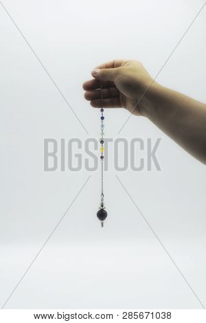 Pendulum Dowsing On An Isolated White Background With An Amethyst Crystal And Colored Chakra Stones.