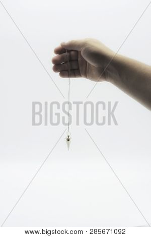 Pendulum Dowsing On An Isolated White Background With A Silver Point.