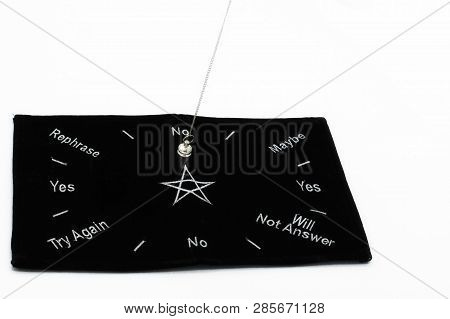 Pendulum Dowsing On An Isolated White Background With A Silver Point And A Black Dowsing Matt.