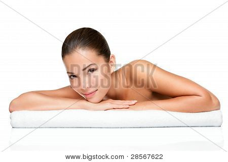 Spa beauty skin treatment woman on white towel. Gorgeous beutiful multiracial Caucasian / Asian female model with perfect skin lying on towel having beauty treatment at spa. Young woman in her 20s isolated on white background. poster