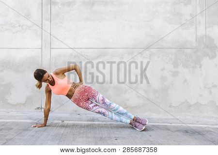 Fitness woman in colorful sportswear doing workout on the city street over gray concrete background. Outdoor sports clothing and shoes, urban style.