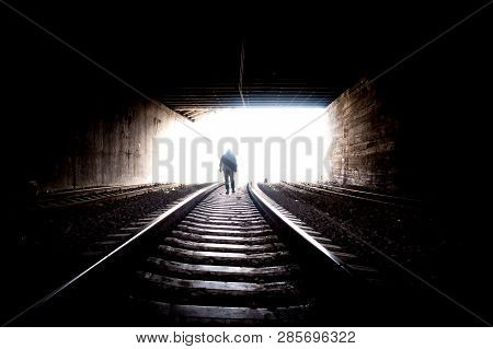 Man On Railway. Young Man Going On Rails To The Bright Light In The End On A Tunnel. Man In Tunnel G