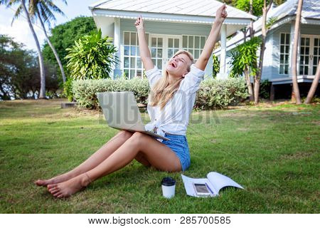 Beautiful Blonde Girl With A Laptop On A Green Lawn, Education And Distant Work, Spring And Summer