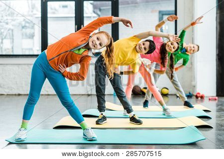 Smiling Preteen Kids Doing Sport Exercise Together