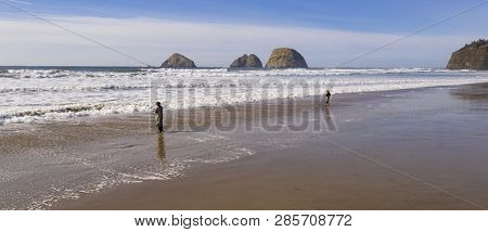 Two Guys Fishing In The Ocean Surf Near Oceanside Oregon On The Pacific