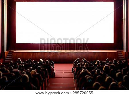 Cinema Empty Screen With Audience. Blurred People Silhouettes Watching Movie Performance. Copy Space