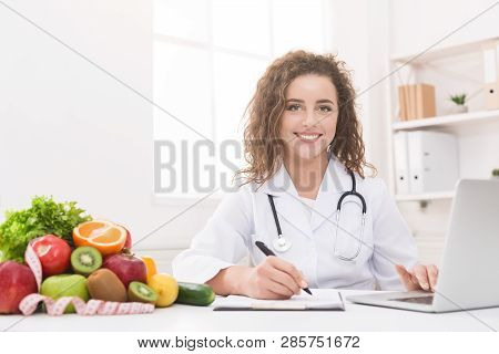 Modern Health Care. Nutritionist Working With Laptop And Writing On Paperwork, Empty Space
