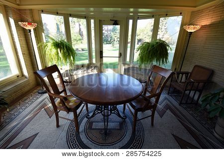 beautiful dinning room setup in a room surrounded by glass windows with two chairs and a round table poster