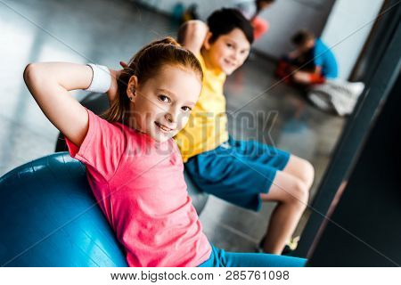 Smiling Kids Doing Abs Exercise With Fitness Balls In Gym