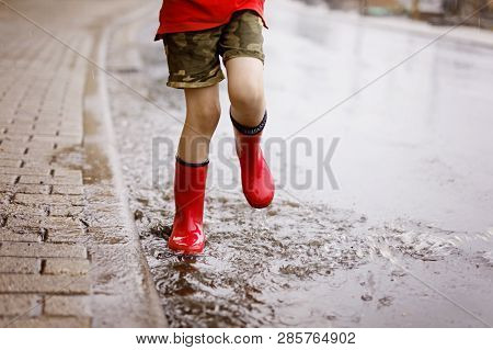 Child Wearing Red Rain Boots Jumping Into A Puddle. Close Up. Kid Having Fun With Splashing With Wat