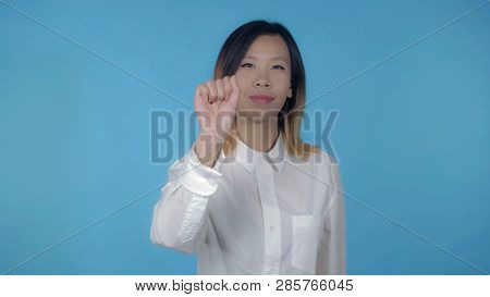 Young Asian Woman Posing Showing Hand Gesture Attention On Blue Background In Studio. Attractive Mil