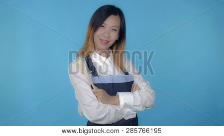 Young Asian Woman Posing With Spoon Wearing Like Cook On Blue Background In Studio. Attractive Mille