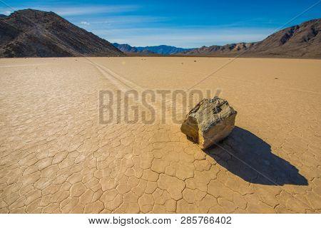 Wandering Rocks on Desert Salt Mud Flat Moving Trails Path