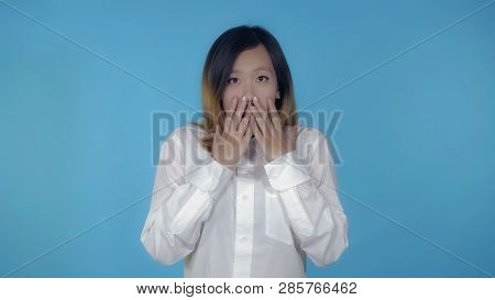 Young Asian Woman Posing Showing Feeling Of Fear On Blue Background In Studio. Attractive Millennial