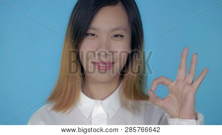 Close Up Portrait Young Asian Woman Laughing Shows Sign Symbol Ok On Blue Background In Studio. Attr