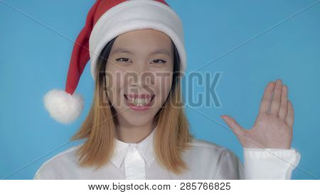 Close Up Portrait Young Asian Woman Waving Hand Say Hello Wearing Santa Claus Hat On Blue Background