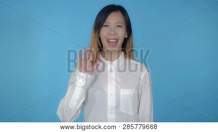 Young Asian Woman Posing Showing Hand Gesture Hello On Blue Background In Studio. Attractive Millenn