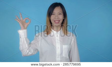 Young Asian Woman Posing Showing Hand Gesture Ok On Blue Background In Studio. Attractive Millennial