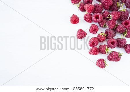 Sprinkled Raspberries On White Background. Ripe Raspberries With Copy Space For Text. Raspberry On A