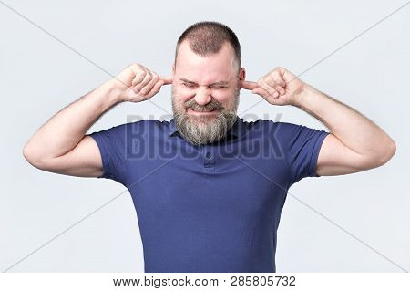 Senior Man, Covering Closed Ears Annoyed By Loud Noise Not Wanting To Hear Story