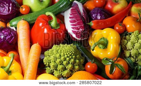 Fruits And Vegetables Concept With Fresh Organic Vegetables And Assorted Variety Of Fruits Scattered