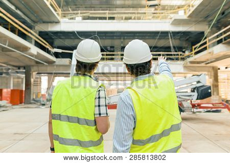 Male Building Workers Working At Construction Site, Back View. Building, Development, Teamwork And P